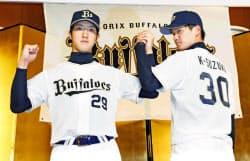 オリックスの新入団記者会見でポーズをとる田嶋大樹投手(左)と鈴木康平投手(17日、大阪市)=共同