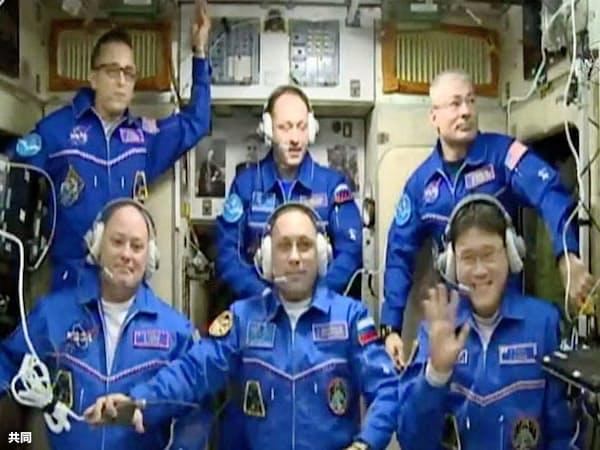 国際宇宙ステーションに到着し、カメラに向かって笑顔で手を振る金井宣茂さん(前列右、19日)=NASAテレビ・共同