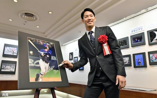 中部報道展が開幕し、自身の写真にサインするプロ野球中日の京田陽太内野手(20日、名古屋市)=共同