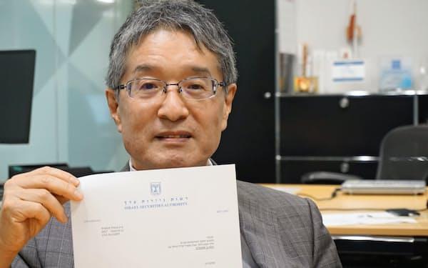 テルアビブ証券取引所の上場承認の証書を示すインターネット総合研究所の藤原洋所長