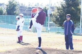 ブルペンで投球練習する浅利(中央)とフォームを指導する荻野さん(右端)