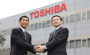 東芝メモリ四日市工場で握手する成毛社長(右)とベインキャピタルの杉本日本代表(13日午後、三重県四日市市)