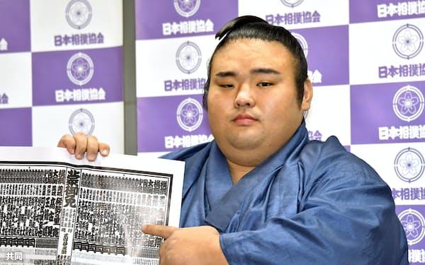 大相撲初場所の番付表を手にする新小結の貴景勝(26日、東京・両国国技館)=共同
