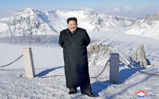 白頭山の山頂にある天池の畔に立つ金正恩氏=朝鮮通信・共同
