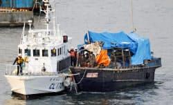 海上保安庁の巡視艇にえい航されて函館港に入る北朝鮮の木造船(12月9日、北海道函館市)=共同