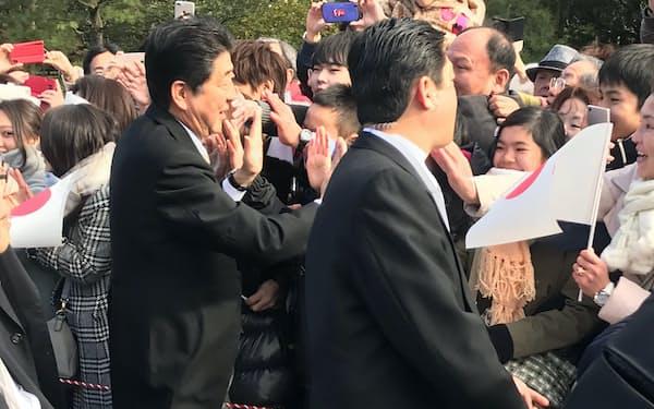 伊勢神宮内宮で参拝客に駆け寄り、ハイタッチする首相(4日午後、伊勢神宮)