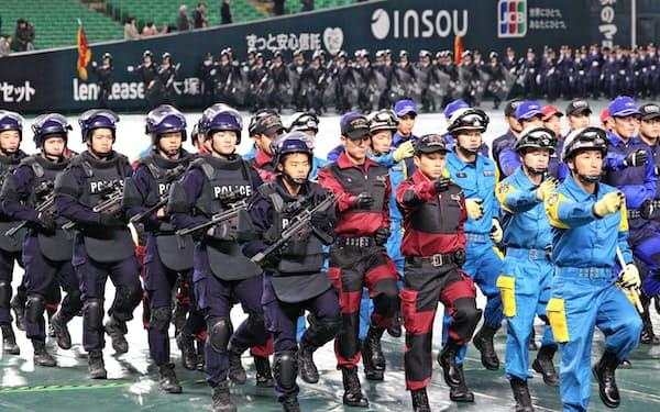 年頭視閲で行進する警察官(10日午前、福岡市中央区のヤフオクドーム)