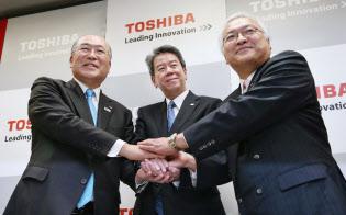 確執を押し殺して握手する(左から)西田会長、田中社長、佐々木副会長(肩書は2013年当時)