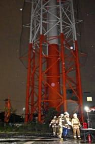 放送の中断を受け、石川テレビの敷地内にある送信鉄塔を調べる消防隊員(10日夜、金沢市)=共同