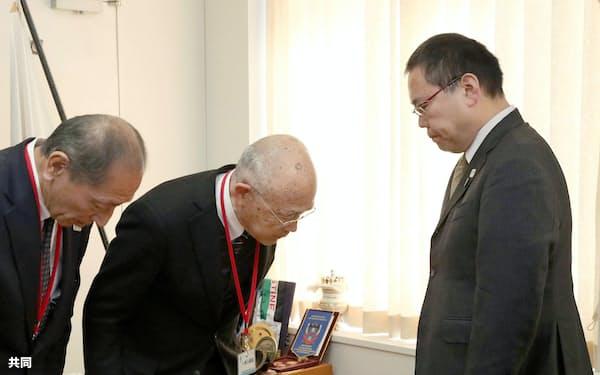 スポーツ庁を訪問し、今里譲次長(右)に謝罪する日本カヌー連盟の成田昌憲会長(中央)ら(11日午前、同庁)=共同