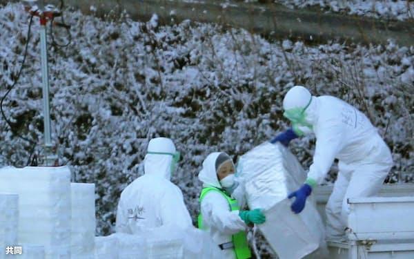 高病原性鳥インフルエンザが確認された養鶏場の周辺で作業する関係者(12日午前、香川県さぬき市)=共同