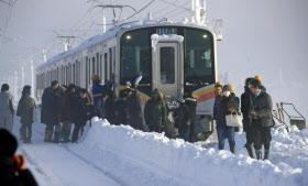 立ち往生したJR信越線の電車から避難する乗客(12日午前、新潟県三条市)