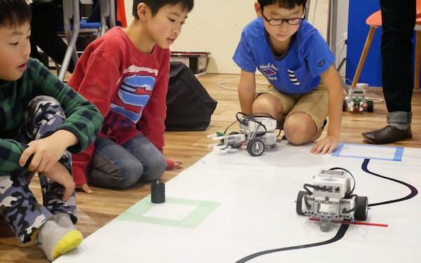 小学生らが自分でプログラムを作成してロボットを動かす(大阪府堺市の教室「ロボ団」)