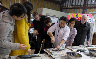 訪日外国人は魚さばき体験に興奮気味(鳥取市)