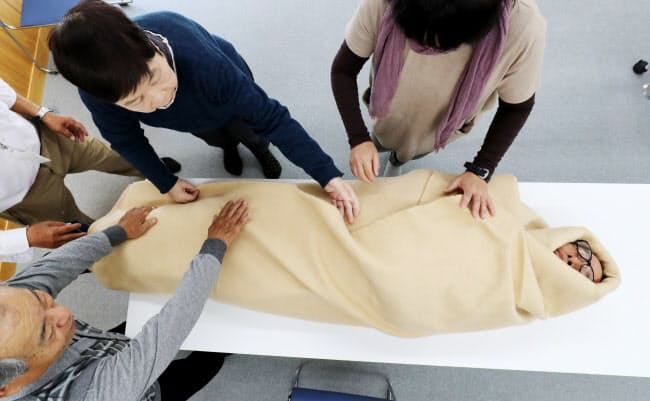 町が開いた防災研修で、防災士から毛布の巻き方を学ぶ住民