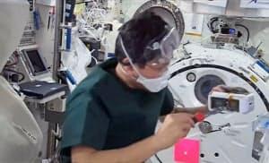 国際宇宙ステーションの日本実験棟「きぼう」でたんぱく質の結晶化実験をする金井宣茂宇宙飛行士(JAXA/NASA提供)