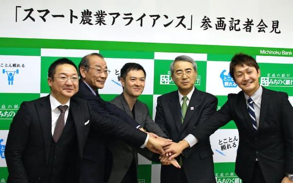 アライアンス参画の記者会見で握手するオプティムの菅谷俊二社長(中央)ら関係者(青森市のみちのく銀行本店)