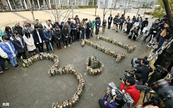 竹灯籠を前に、東日本大震災の発生時刻に合わせて黙とうする東北から訪れた被災者ら(17日、神戸市中央区)=共同