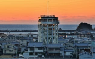 朝焼けに染まる静かな港町に高さ22メートルの津波避難タワーがそびえる(高知県黒潮町)=淡嶋健人撮影