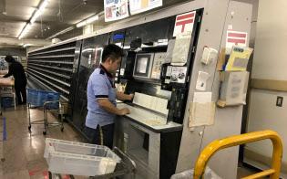 昨年末の郵便局では、職員が年賀はがきの集配作業に追われていた(17年12月26日、東京都新宿区の新宿郵便局)
