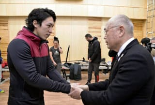 競技団体がアスリートに対する意識を変える必要がある(日本カヌー連盟の成田昌憲会長=右=と握手する小松正治選手)=共同