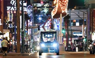 ネオンに彩られたラスベガスの街を巡回するドライバーのいない自動運転バス。観光客などを乗せ約1キロの公道を静かに走る(17日)=井上昭義撮影