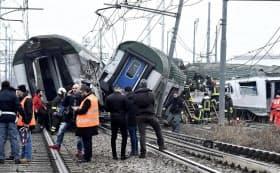 ミラノ近郊で脱線した列車から乗客を救出するレスキュー隊(25日)=AP