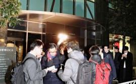 26日午後、仮想通貨取引所の運営大手コインチェックの本社が入るビルに集まった利用者ら(共同)