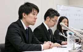 記者会見するコインチェックの和田晃一良社長(左)ら(26日夜、東証)