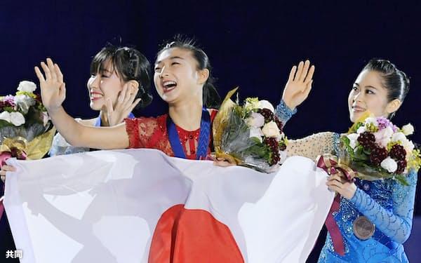 女子で表彰台を独占した日本勢。スタンドの歓声に応える(左から)2位の三原舞依、優勝した坂本花織、3位の宮原知子(26日、台北)=共同