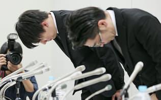 記者会見を終え、頭を下げるコインチェックの和田晃一良社長(左、27日未明、東証)