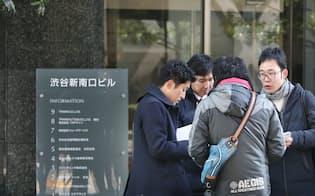 コインチェックが入るビルを訪れた利用客や報道陣ら(27日午前、東京都渋谷区)