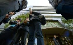 コインチェックが入るビル前を訪れた利用者(手前左)ら(27日午前、東京都渋谷区)