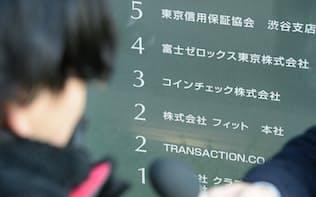 コインチェックが入るビル前に訪れた利用客(左)(27日午前、東京都渋谷区)