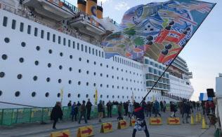 着岸したクルーズ船から降り立つ乗客を大旗が歓迎(29日午前、高知市)