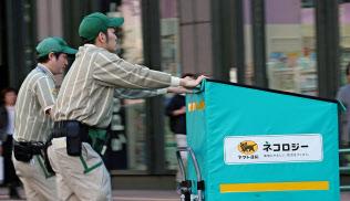 運賃上げで損益は改善した(荷物を配送するヤマト運輸の従業員、東京都中央区)