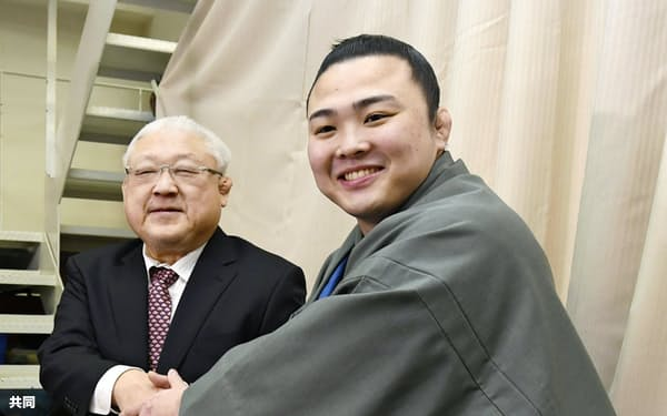 新十両昇進を決め、宮城野親方(左)と握手する炎鵬(31日、東京都墨田区の宮城野部屋)=共同