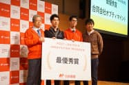 日本郵便のプログラムで最優秀賞を受賞したオプティマインドの松下代表(左から2人目)と、日本郵便の横山社長(左)=1日、都内