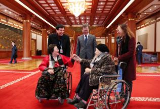 車いすに乗る元慰安婦らを昼食会に招いた文大統領(中央、ソウル)=韓国大統領府提供