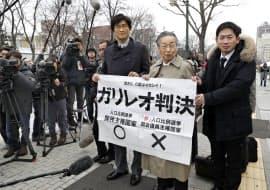 衆院選の「1票の格差」を巡る訴訟の判決を受け、札幌高裁前で紙を掲げる原告側の弁護士(6日午後)=共同