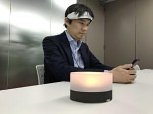 頭部に装着した計測装置が脳の活動データを無線通信で照明器(手前)に送り、赤色や青色に変化して脳の状態の変化を映し出す