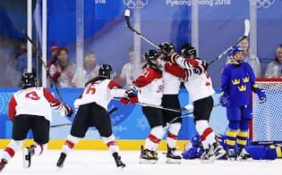 日本―スウェーデン 第2ピリオド、同点ゴールを決めた浮田(左から4人目)に駆け寄って喜ぶ日本の選手たち(10日、江陵)=共同