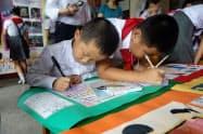 日韓の子に向けたメッセージを書く平壌の小学生(昨年8月)=日本国際ボランティアセンター提供)