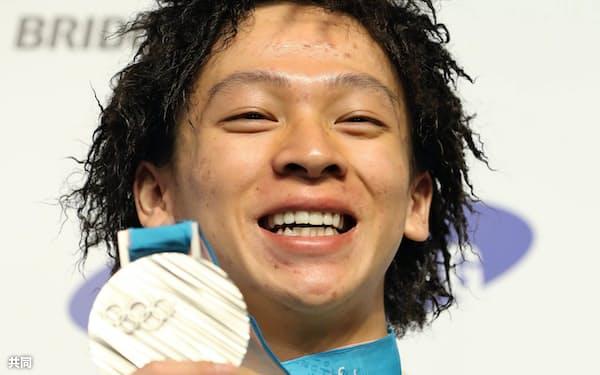 獲得した銀メダルを手に笑顔のスノーボード男子ハーフパイプの平野選手(15日、平昌)=共同