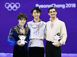 フィギュアスケート男子で金メダルを獲得し、セレモニーで笑顔を見せる羽生結弦(中央)。左は銀の宇野昌磨、右は銅のハビエル・フェルナンデス(17日、江陵)=共同