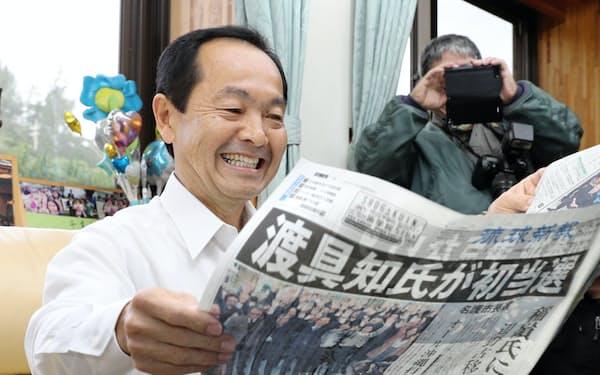名護市長選から一夜が明け、地元紙に目を通す渡具知氏(5日、沖縄県名護市)