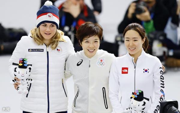 女子500メートルで金メダルを獲得し、セレモニーで笑顔の小平奈緒。右は銀メダルの韓国の李相花、左は銅メダルのチェコのカロリナ・エルバノバ(18日、江陵)=共同