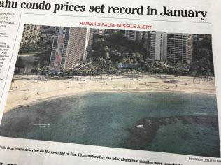 誤警報時、人けがなくなったワイキキ・ビーチの写真を掲載する地元紙