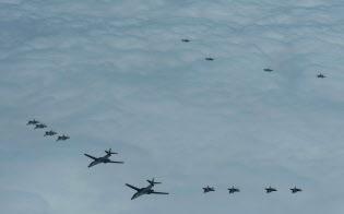 空自戦闘機F15(手前左)は米空軍B1戦略爆撃機(中央)を護衛しながら飛行した