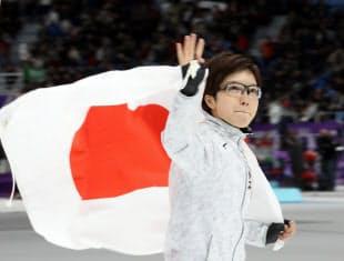 女子500メートルで優勝し、日の丸を掲げ観客の声援に応える小平=上間孝司撮影